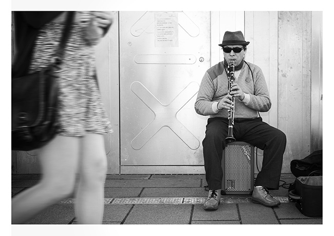 Busker playing the clarinet on the Golden Jubilee pedestrian bridge, London.