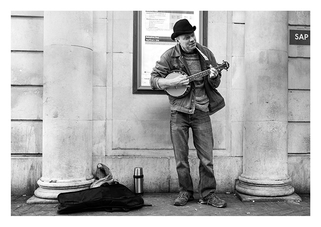 Banjo player, busking at the Embankment Station, London Underground.