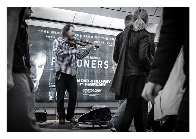 Matt Grabham playing the fiddle, busking in the London Underground.